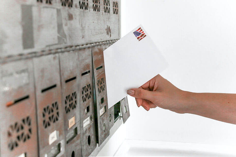 A person inserting a letter into a mailbox