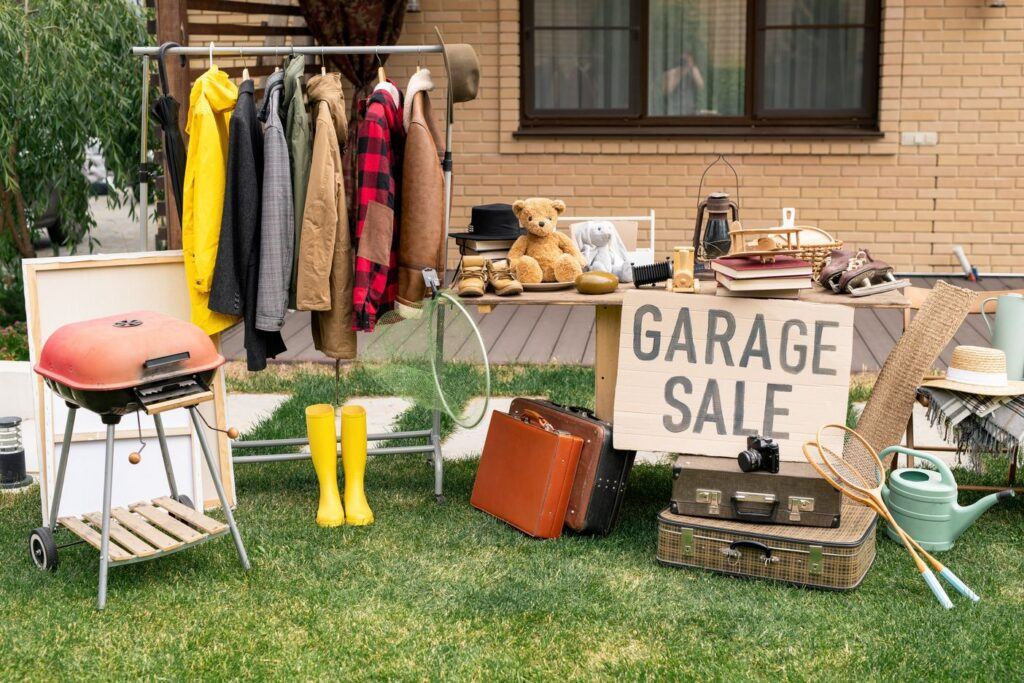 Clothes on the rack, a sign, and a table with stuff in the backyard