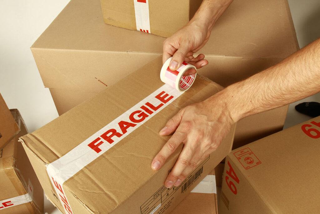 Man labeling a cardboard package