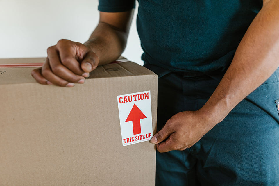 Movers in Philadelphia, PA, getting ready to move a fragile box
