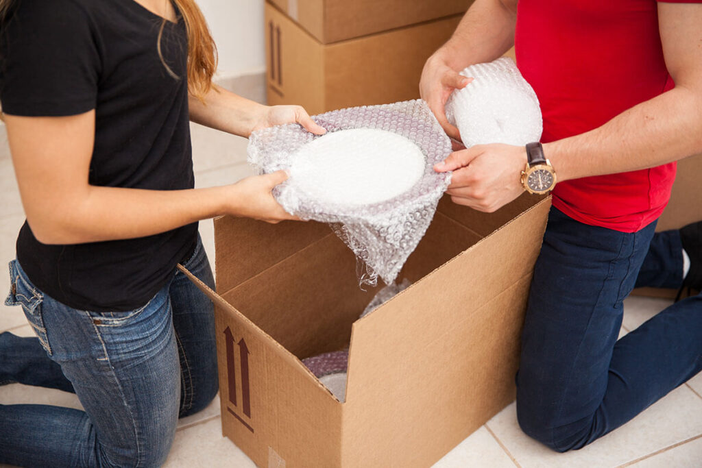 Man and woman putting a wrapped plate in a package