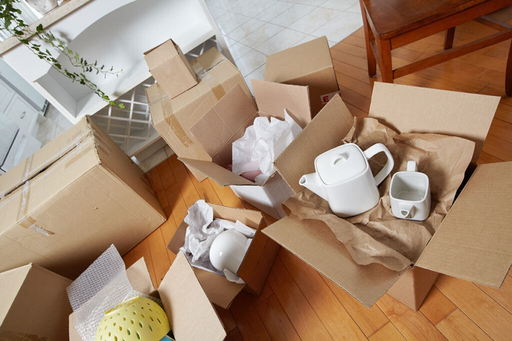 Teapots on cardboard on the floor, packages around them