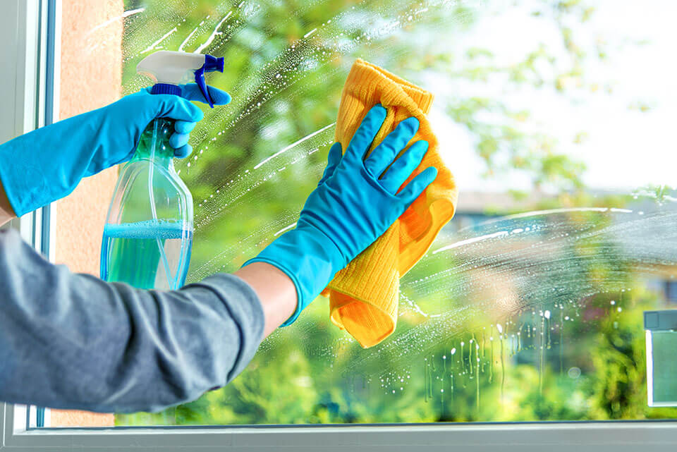A hand with gloves wiping a window