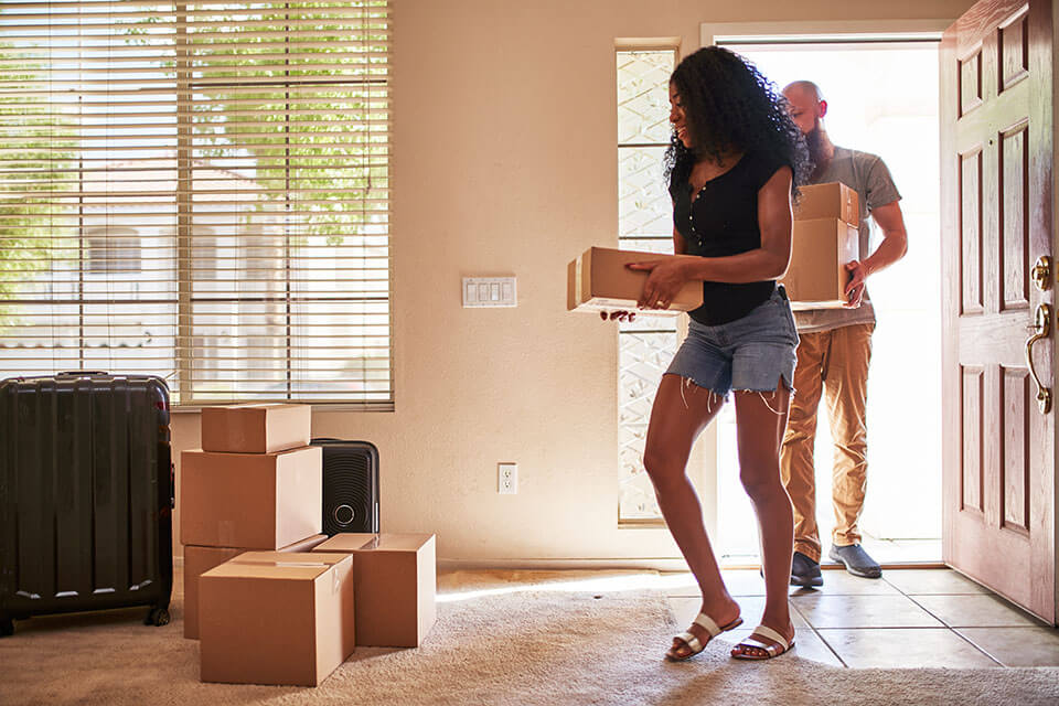A man and a woman taking boxes into a new apartment