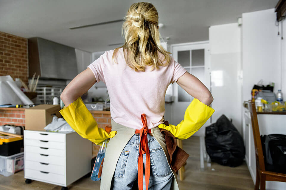 Woman with gloves facing an unpacked kitchen