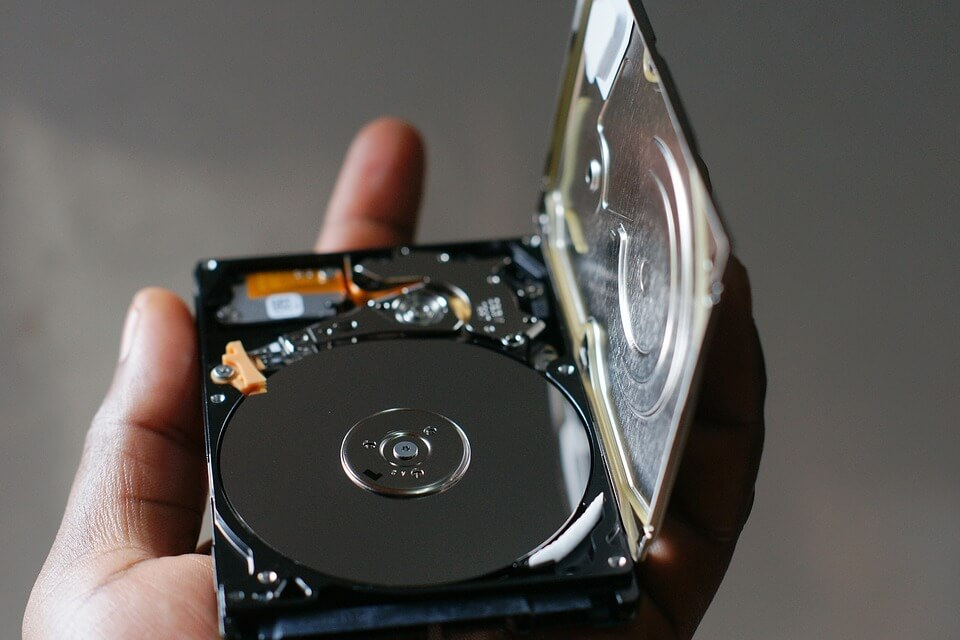 A person holding a computer hard drive