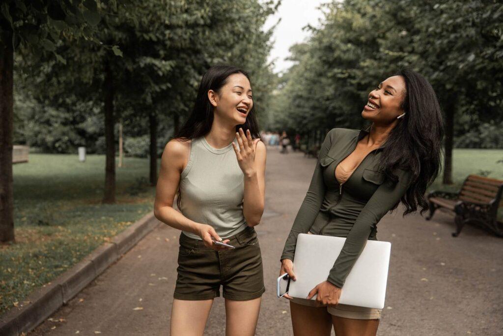 Two gossip girls whispering on-ear a secret standing