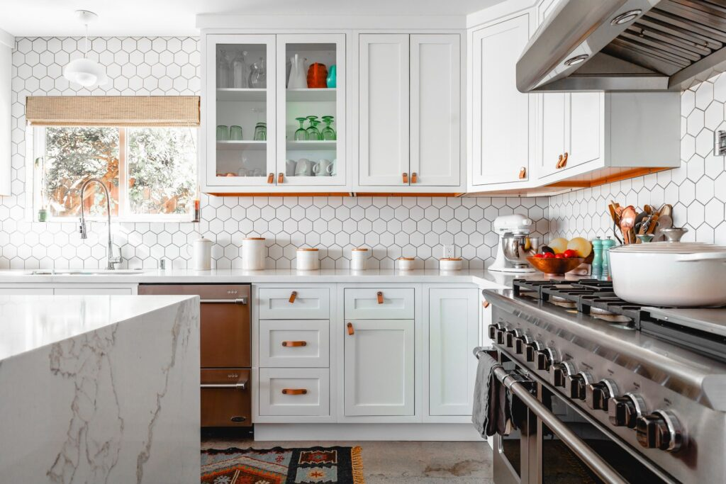 Kitchen with white elements, window, and gray stove