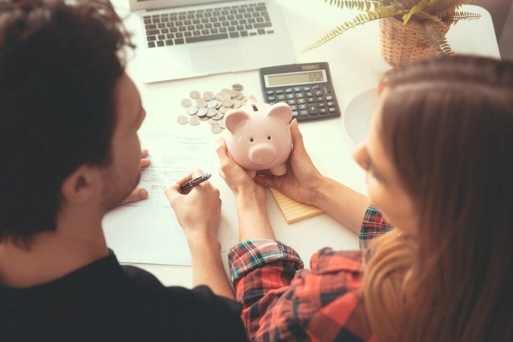 Man and woman sitting at the desk, laptop, coins, and piggy bank on the desk