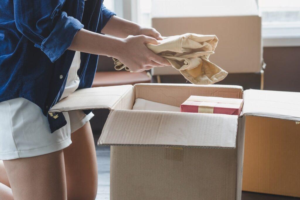 Woman placing a shirt into a carton