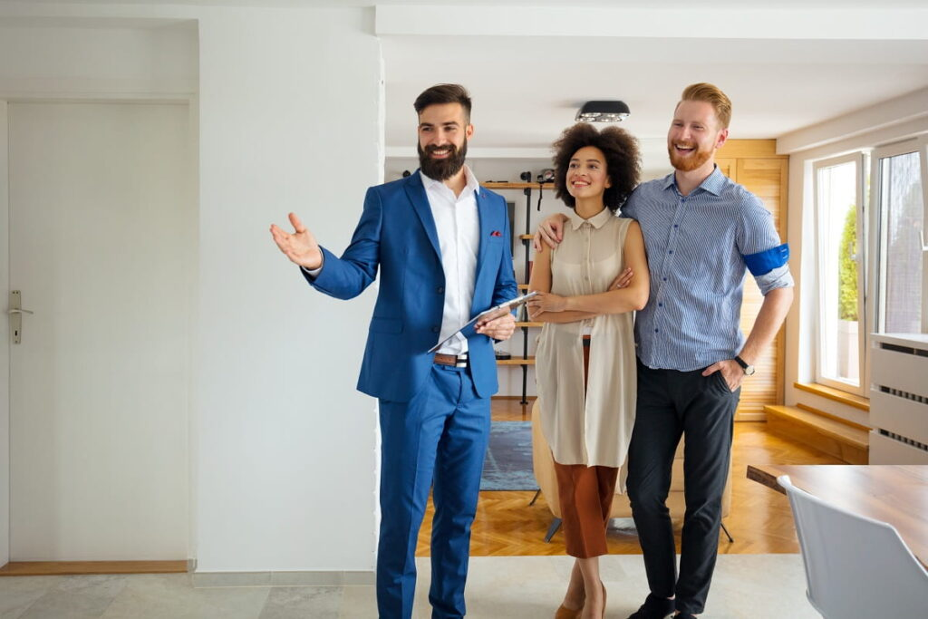 A realtor in a blue suit showing a place to a couple